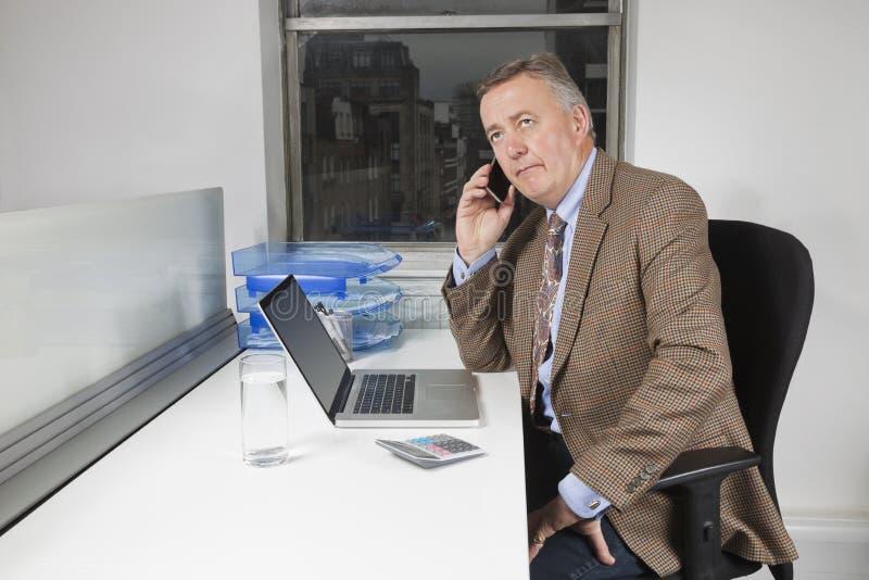 Medelålders affärsman som framme använder mobiltelefonen av bärbara datorn på skrivbordet i regeringsställning royaltyfria bilder