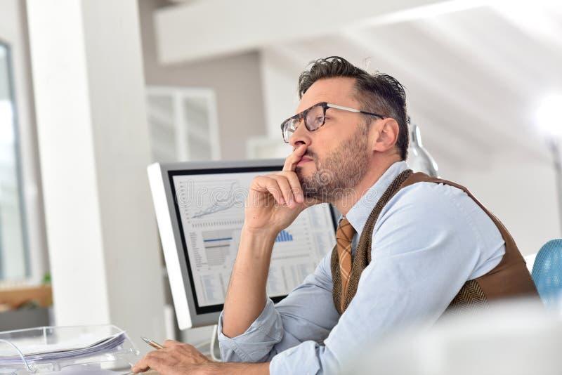 Medelålders affärsman som tänker och arbetar arkivfoton