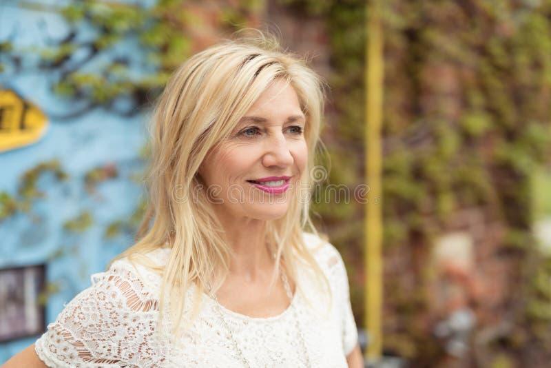 Medelålders blond kvinna med ett fridfullt uttryck arkivfoton