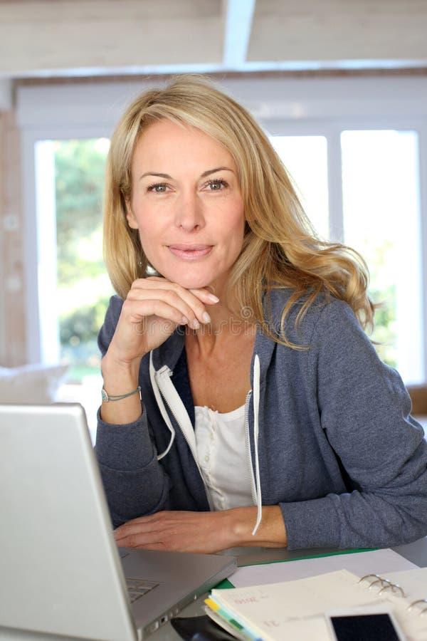 Medelålders blond kvinna som arbetar på bärbara datorn royaltyfri foto