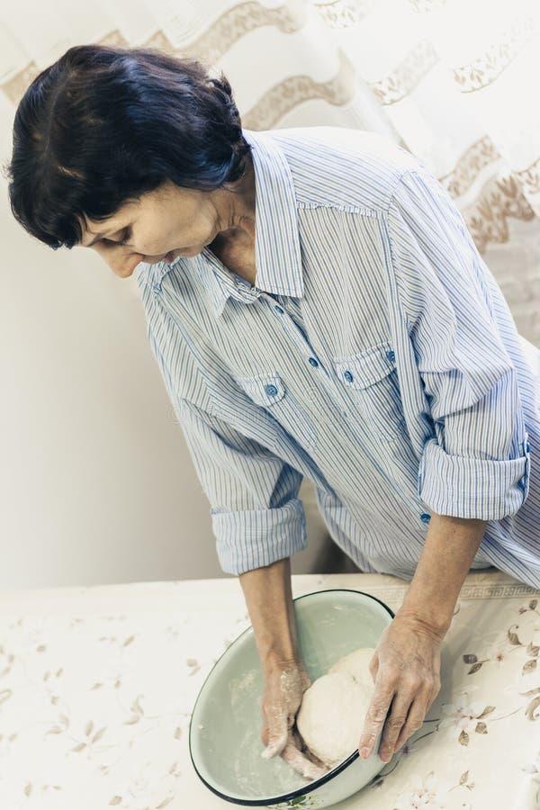 Medelålders brunettkvinna som knådar göra deg för klimpar i blå bunke arkivbild