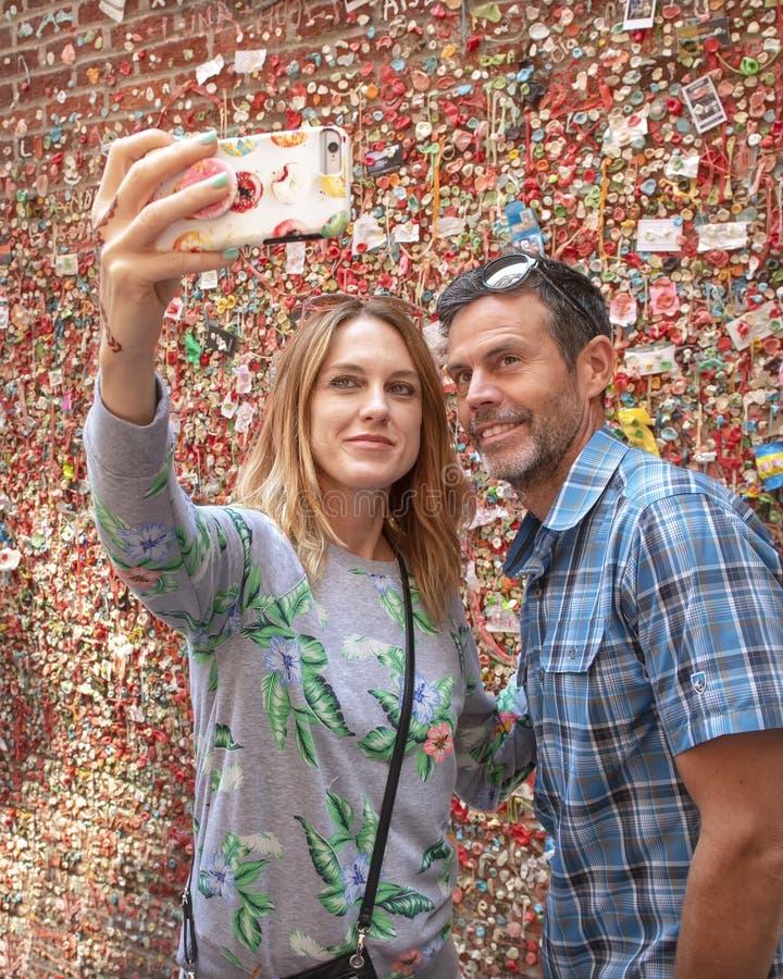 Medelålders fru och make som framme tar en selfie av väggen för marknadsteatergummi, marknad för pikställe, Seattle, Washington royaltyfria bilder