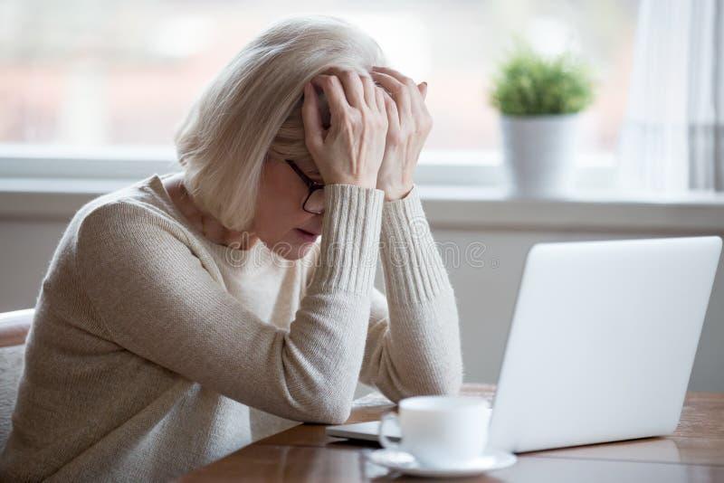 Medelålders kvinna framme av bärbara datorn som frustreras av dåliga nyheter arkivbild