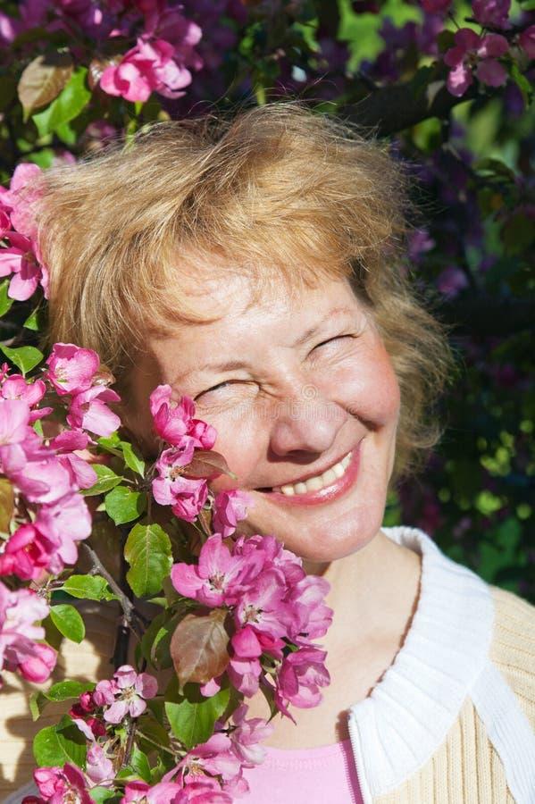 Medelålders kvinna i blomstra magnolias royaltyfri fotografi