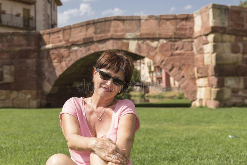 Medelålders kvinna i en le stående royaltyfri bild