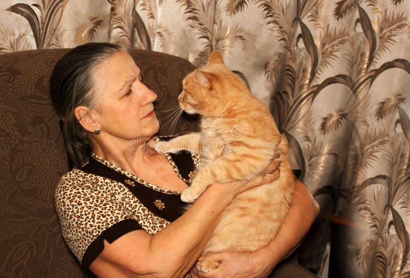 medelålders kvinna med den röda katten royaltyfria foton
