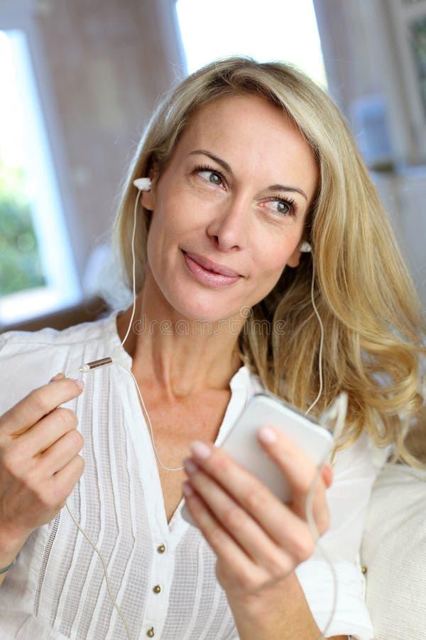 Medelålders kvinna med hörlurar och smartphonen royaltyfri bild
