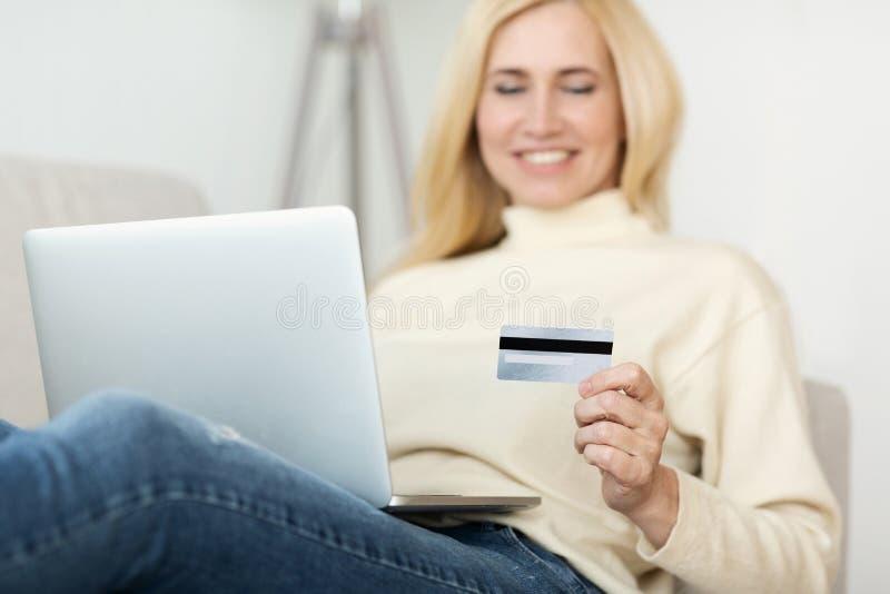 Medelålders kvinna som använder kreditkorten för att betala fotografering för bildbyråer
