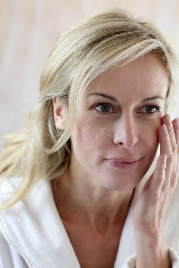 Medelålders kvinna som applicerar skönhetsmedel arkivbild