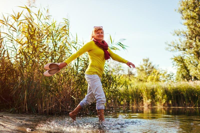 Medelålders kvinna som går på flodbanken på höstdag Hög dam som har gyckel i skogen som tycker om naturen fotografering för bildbyråer