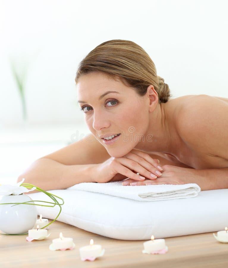 Medelålders kvinna som ligger på massagesäng arkivbild