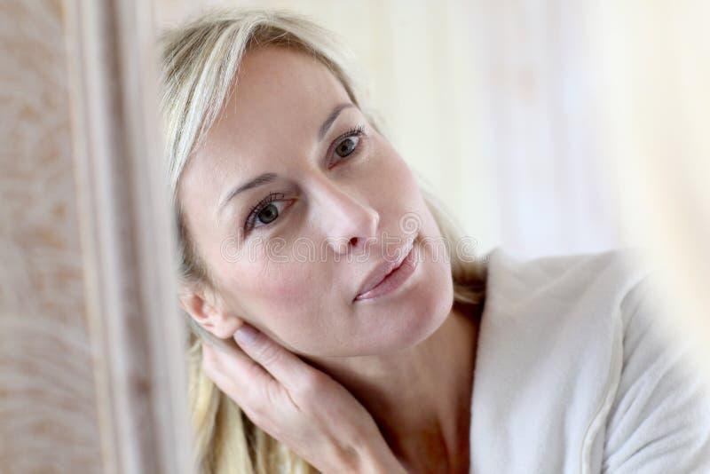 Medelålders kvinna som ser spegeln fotografering för bildbyråer