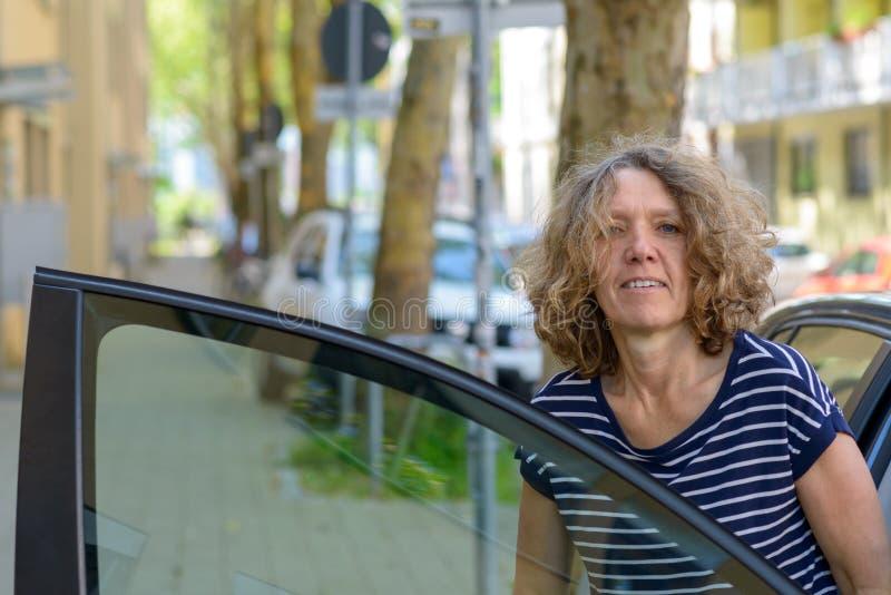 Medelålders kvinna som stiger av från en bil arkivbilder