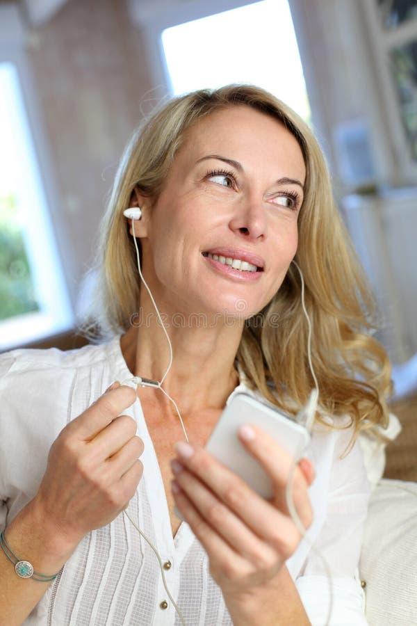Medelålders kvinna som talar på telefonen med hörlurar arkivfoto