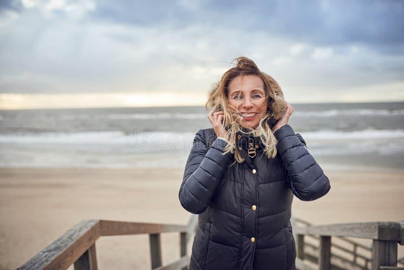 Medelålders kvinna som trotsar en kall vinterdag arkivfoto