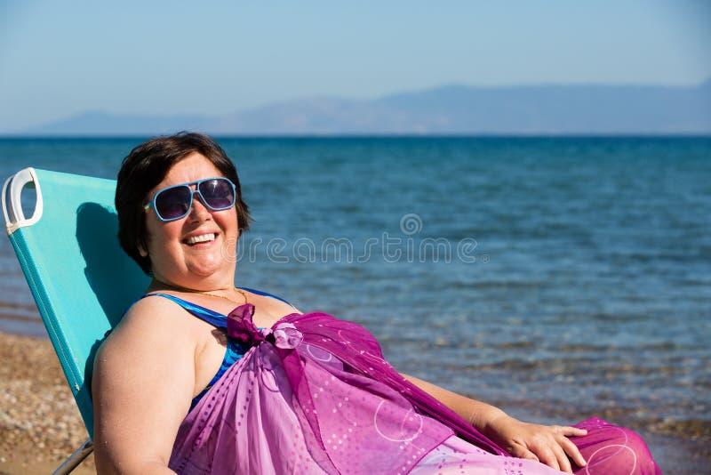 Medelålders kvinna som vilar på havet royaltyfri fotografi