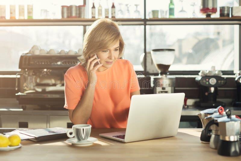 Medelålders kvinnabarista som arbetar på bärbara datorn och talar på smartphonen arkivbild