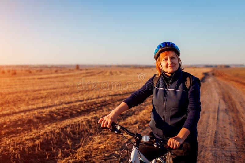 Medelålders kvinnacyklistridning i höstfält på solnedgången Hög idrottskvinna som tycker om hobby royaltyfri fotografi