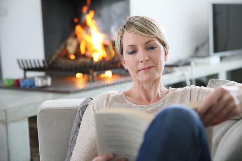 Medelålders kvinnaläsebok hemma royaltyfria bilder