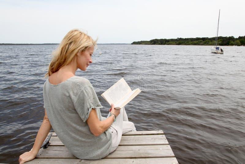 Medelålders kvinnaläsebok vid sjön arkivfoto