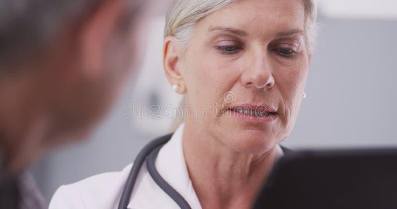Medelålders kvinnlig doktor som ser en minnestavla arkivfoton