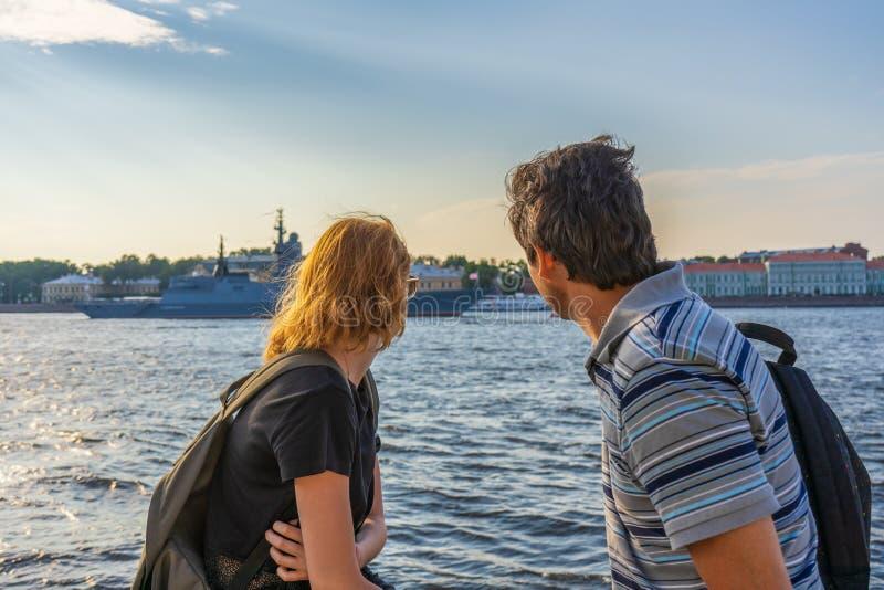 Medelålders mörkhårig man och ung rödhårig mandam på den Neva flodinvallningen som in ser krigsskepp och den arkitektoniska helhe arkivfoto