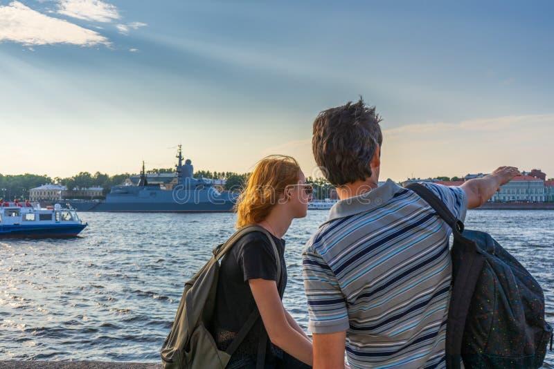 Medelålders mörkhårig man och ung rödhårig mandam på den Neva flodinvallningen som in ser krigsskepp och den arkitektoniska helhe arkivfoton