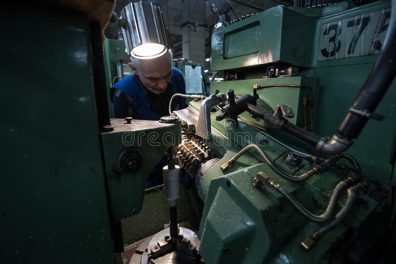 Medelålders man för drejare som arbetar på en malningmaskin arkivfoton