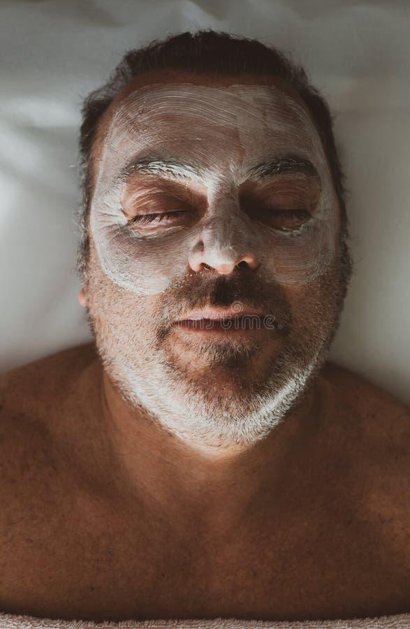Medelålders man i en brunnsort med en ansikts- maskering arkivbild