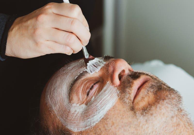 Medelålders man i en brunnsort med en ansikts- maskering arkivfoton
