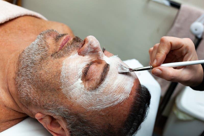 Medelålders man i en brunnsort med en ansikts- maskering royaltyfria bilder