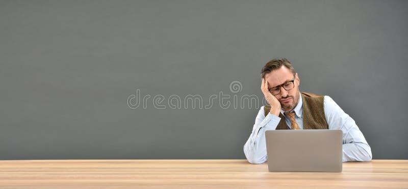 Medelålders man som framme får uttråkad av bärbara datorn arkivfoto