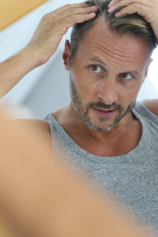 Medelålders man som ser spegeln som kontrollerar hårförlust arkivbilder