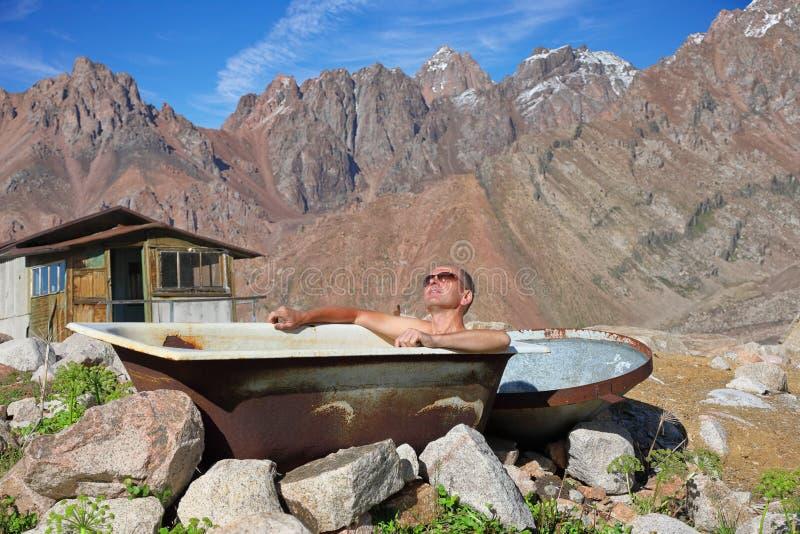 Medelålders man som utomhus tar ett bad arkivbild