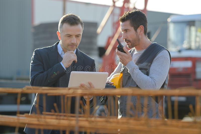 Medelålders manlig arbetare som använder walkie-talkie med kollegan arkivfoton