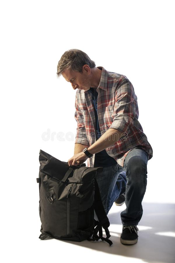 Medelålders manlig turist som packar en ryggsäckLit vid solnedgång royaltyfri foto