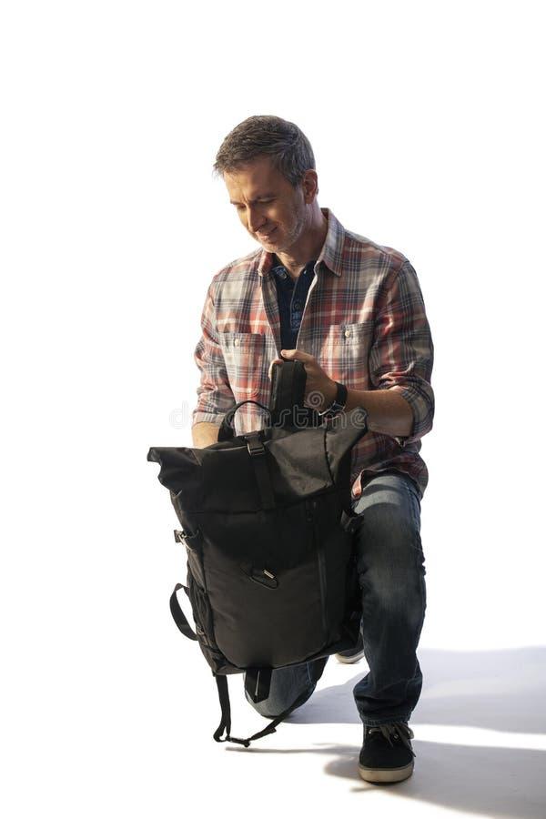 Medelålders manlig turist som packar en ryggsäckLit vid solnedgång royaltyfria bilder