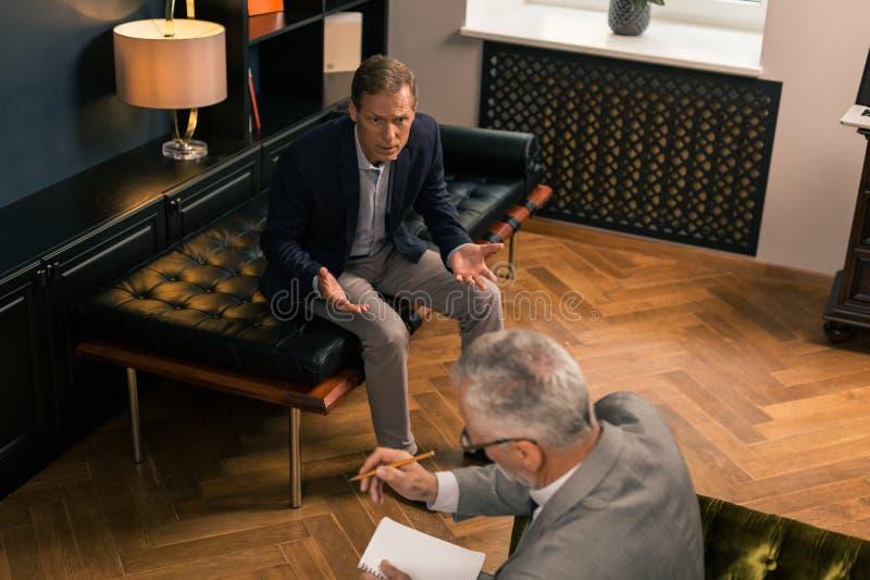 Medelålders orolig man som känslomässigt talar till hans doktor royaltyfri foto