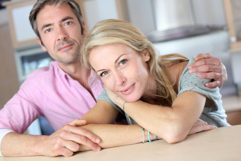 Medelåldersa älska par i köket royaltyfria bilder