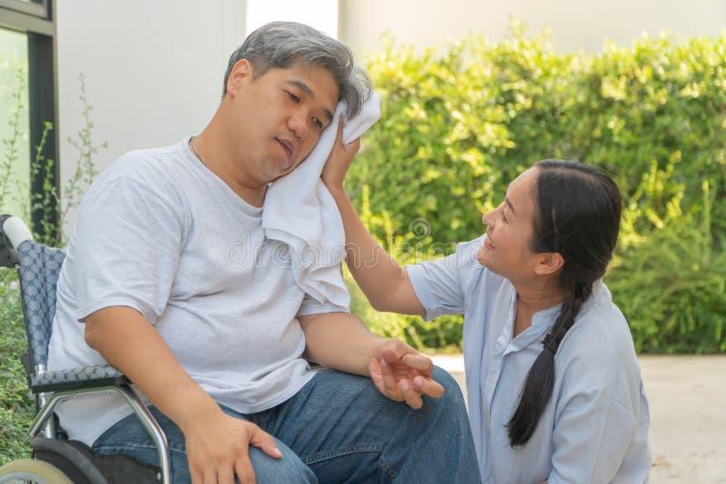Medelåldersa och sjukligt feta män paralyseras, den krokiga munnen, skrynkliga händer, och lemsvagheten i rullstolen och där är e royaltyfri fotografi