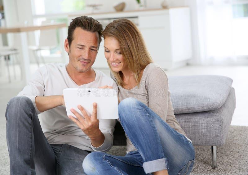 Medelåldersa par genom att använda minnestavlan hemma arkivfoton
