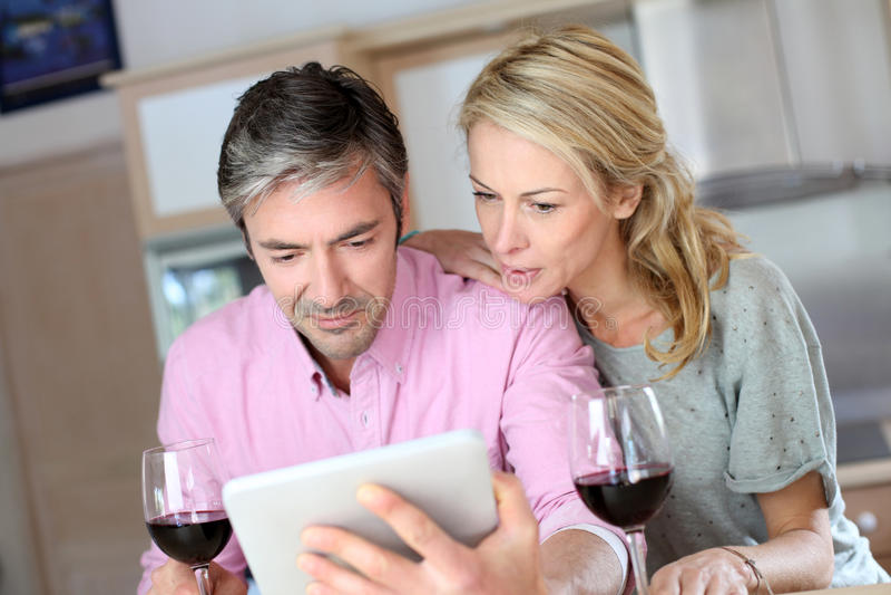 Medelåldersa par i köket som dricker vin arkivfoton