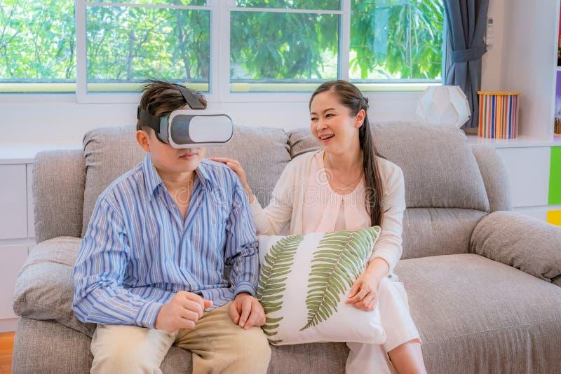 Medelåldersa par, män som försöker att spela VR-exponeringsglas, kvinnor som skrattar som män, c arkivbilder