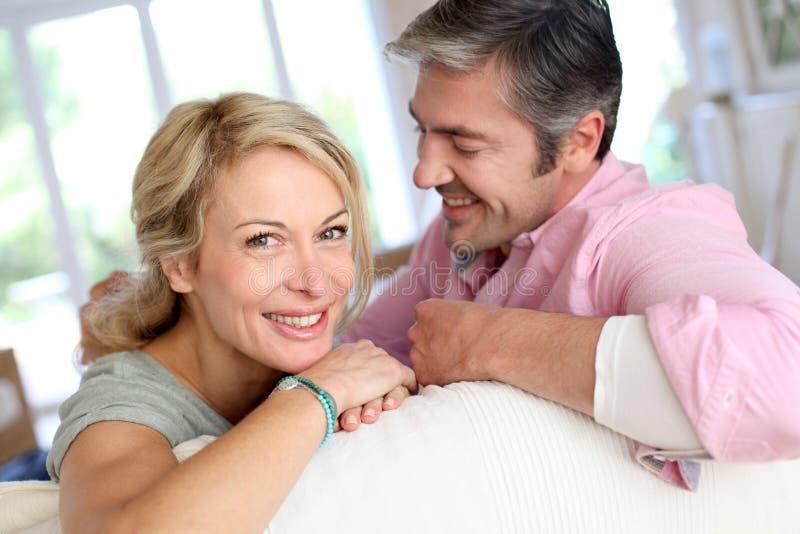 Medelåldersa par som är lyckligt hemmastatt royaltyfri bild