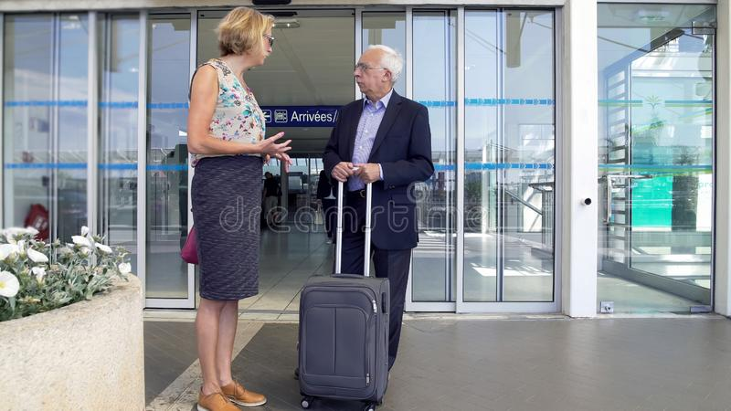 Medelåldersa par som diskuterar plan som står nära flygplatsen, folk på semester arkivfoton