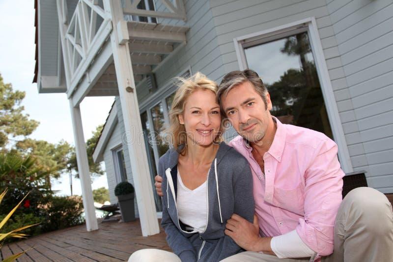 Medelåldersa par som framme sitter av deras hem arkivbild