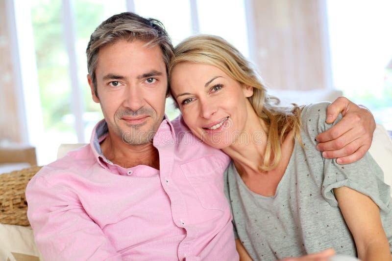 Medelåldersa par som hemma sitter royaltyfria foton