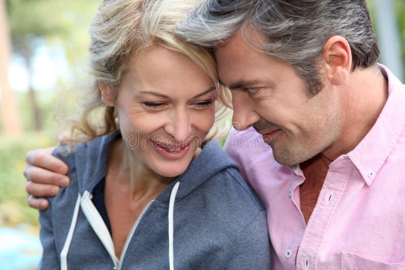 Medelåldersa par som ler utomhus royaltyfria bilder