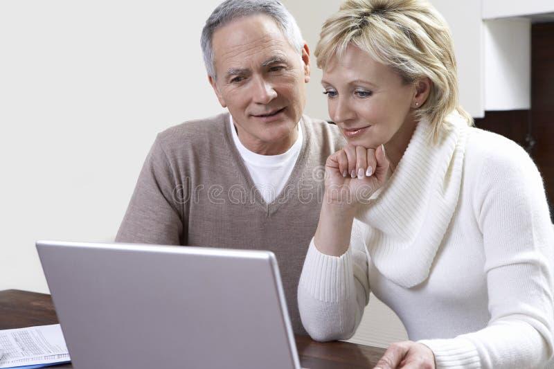 Medelåldersa par som räknar räkningar genom att använda bärbara datorn i kök arkivfoto