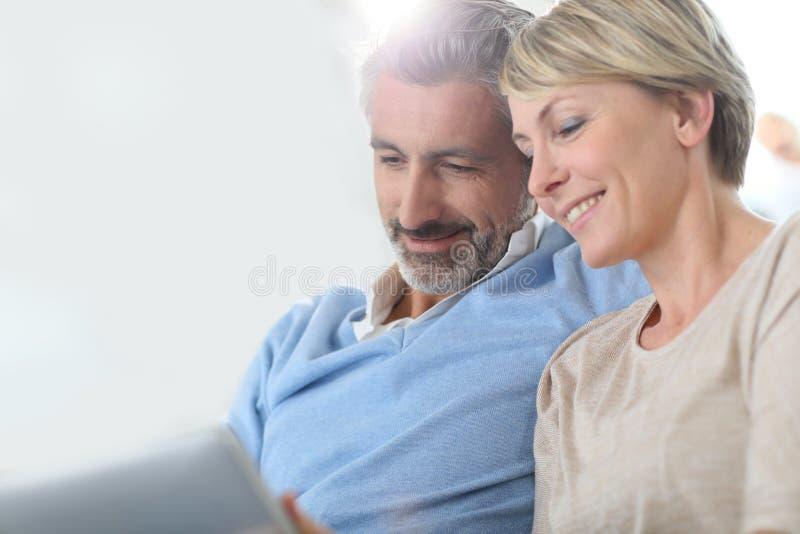 Medelåldersa par som tillsammans websurfing arkivbild